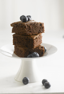 Brownie cake with blueberries on dessert stand, close-upの写真素材 [FYI04345898]