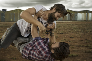 wo men with full beards fighting in abandoned landscapeの写真素材 [FYI04345960]