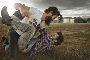 Two men with full beards fighting in abandoned landscapeの写真素材 [FYI04345962]