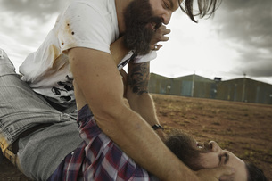Two men with full beards fighting in abandoned landscapeの写真素材 [FYI04345963]