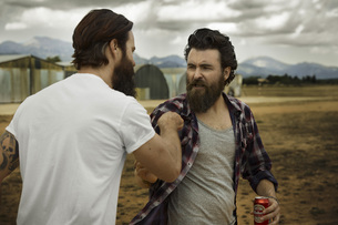 wo men with full beards fighting in abandoned landscapeの写真素材 [FYI04345965]