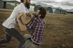 Two men with full beards fighting in abandoned landscapeの写真素材 [FYI04345973]