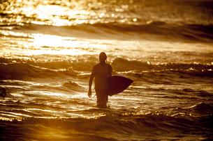 Indonesia, Bali, man with surfboard at twilightの写真素材 [FYI04346009]