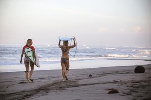 Indonesia, Bali, two women carrying surfboards on the beachの写真素材 [FYI04346010]