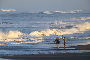 Indonesia, Bali, two women carrying surfboards at seafrontの写真素材 [FYI04346013]