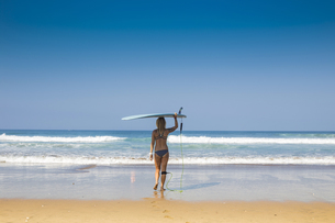 Indonesia, Bali, back view of woman carrying her surfboard oの写真素材 [FYI04346070]