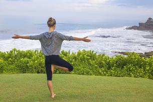 Indonesia, Bali, Tanah Lot, woman practising yoga at the coaの写真素材 [FYI04346079]