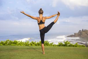Indonesia, Bali, Tanah Lot, woman practising yoga at the coaの写真素材 [FYI04346081]