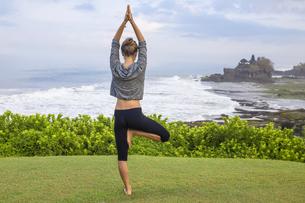 Indonesia, Bali, Tanah Lot, woman practising yoga at the coaの写真素材 [FYI04346082]