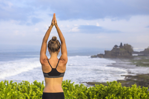 Indonesia, Bali, Tanah Lot, woman practising yoga at the coaの写真素材 [FYI04346083]