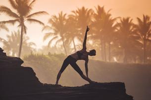 Indonesia, Bali, woman practising yoga at the coast at twiliの写真素材 [FYI04346087]