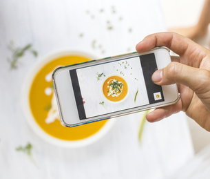 Woman taking a photo of carrot pumpkin soup with her smartphの写真素材 [FYI04346095]