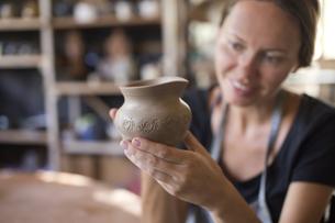 Smiling potter in workshop looking at earthenware jarの写真素材 [FYI04346183]
