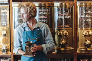 Coffee roaster in his shop holding old-fashioned coffee millの写真素材 [FYI04346377]