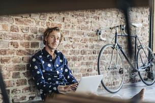 Man sitting at brick wall using laptopの写真素材 [FYI04346383]