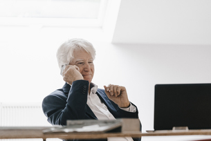 Smiling senior businessman on the phone in his officeの写真素材 [FYI04346411]
