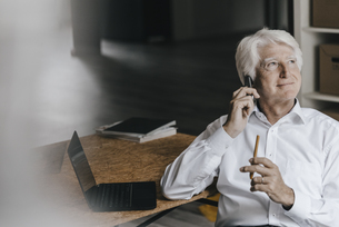 Portrait of smiling senior businessman on the phone in his oの写真素材 [FYI04346416]