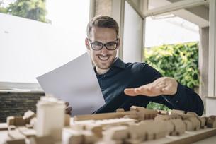 Smiling architect looking at urban development modelの写真素材 [FYI04346451]