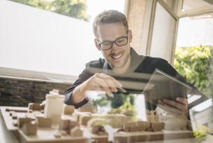 Smiling architect looking at urban development modelの写真素材 [FYI04346456]