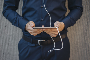 Businessman holding tablet with connected earphonesの写真素材 [FYI04346468]