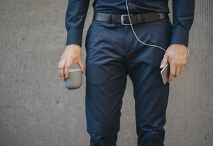 Businessman holding smartphone with connected earphones andの写真素材 [FYI04346477]