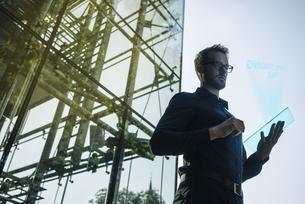 Businessman using futuristic portable deviceの写真素材 [FYI04346494]