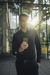 Businessman holding futuristic portable deviceの写真素材 [FYI04346497]