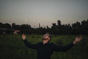 Happy businessman standing in rural field at duskの写真素材 [FYI04346501]