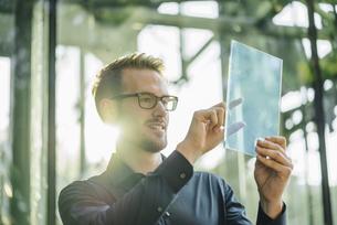 Businessman using futuristic portable deviceの写真素材 [FYI04346522]