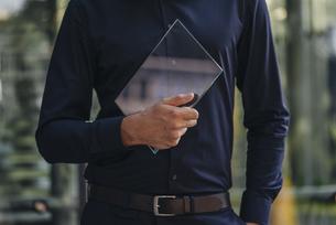 Businessman holding futuristic portable deviceの写真素材 [FYI04346525]