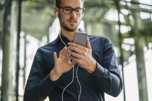 Businessman holding smartphone with connected earphonesの写真素材 [FYI04346527]