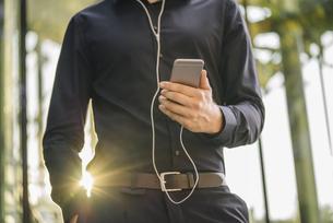 Businessman holding smartphone with connected earphonesの写真素材 [FYI04346528]