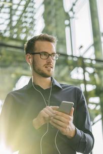 Businessman using smartphone with connected earphonesの写真素材 [FYI04346529]