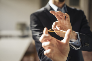 Hands of businessman aiming with rubber band and folded papeの写真素材 [FYI04346554]