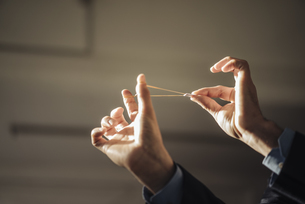 Hands of businessman aiming with rubber band and folded papeの写真素材 [FYI04346555]
