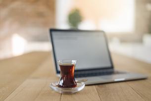 Turkish tea and laptop on tableの写真素材 [FYI04346586]