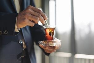 Businessman holding glass of Turkish teaの写真素材 [FYI04346614]