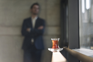 Glass of Turkish tea at the window with businessman in backgの写真素材 [FYI04346616]