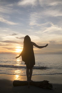 Indonesia, Bali, woman watching the sunset over the ocean baの写真素材 [FYI04346633]