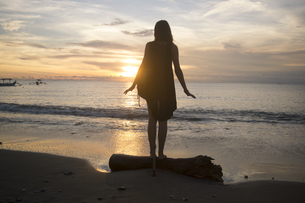 Indonesia, Bali, woman watching the sunset over the oceanの写真素材 [FYI04346634]