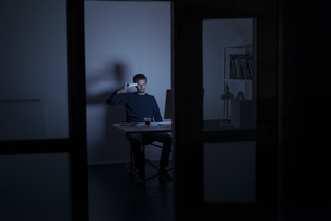 Man working late in office holding gun at his headの写真素材 [FYI04346643]