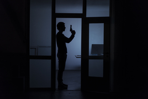 Man standing in office at night holding a gunの写真素材 [FYI04346645]