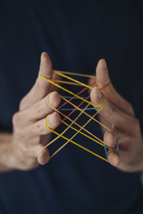 Close-up of man holding rubber bandsの写真素材 [FYI04346652]
