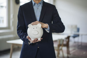 Close-up of businessman holding piggy bankの写真素材 [FYI04346654]