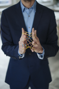 Close-up of businessman holding rubber bandsの写真素材 [FYI04346655]