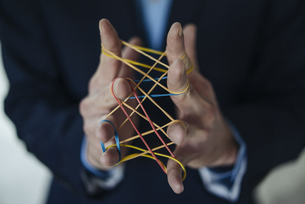 Close-up of businessman holding rubber bandsの写真素材 [FYI04346656]
