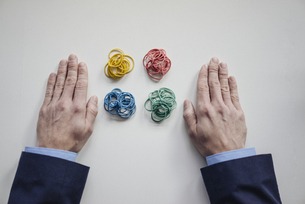 Close-up of businessman's hands next to rubber bandsの写真素材 [FYI04346658]