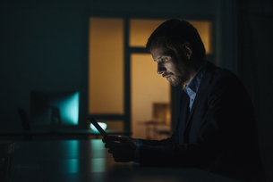 Businessman working late in office using tabletの写真素材 [FYI04346667]