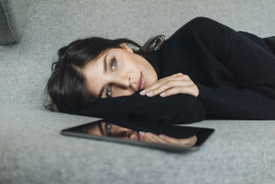 Serious young woman lying on couch next to tabletの写真素材 [FYI04346677]