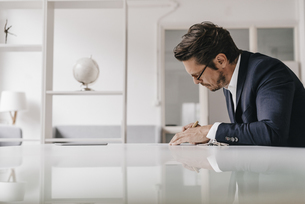 Businessman at table writing in notebookの写真素材 [FYI04346712]
